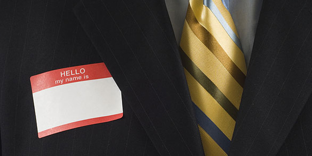 Man in a business suit wearing a blank name tag sticker
