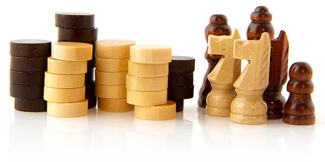 wooden checker and chess pieces facing off